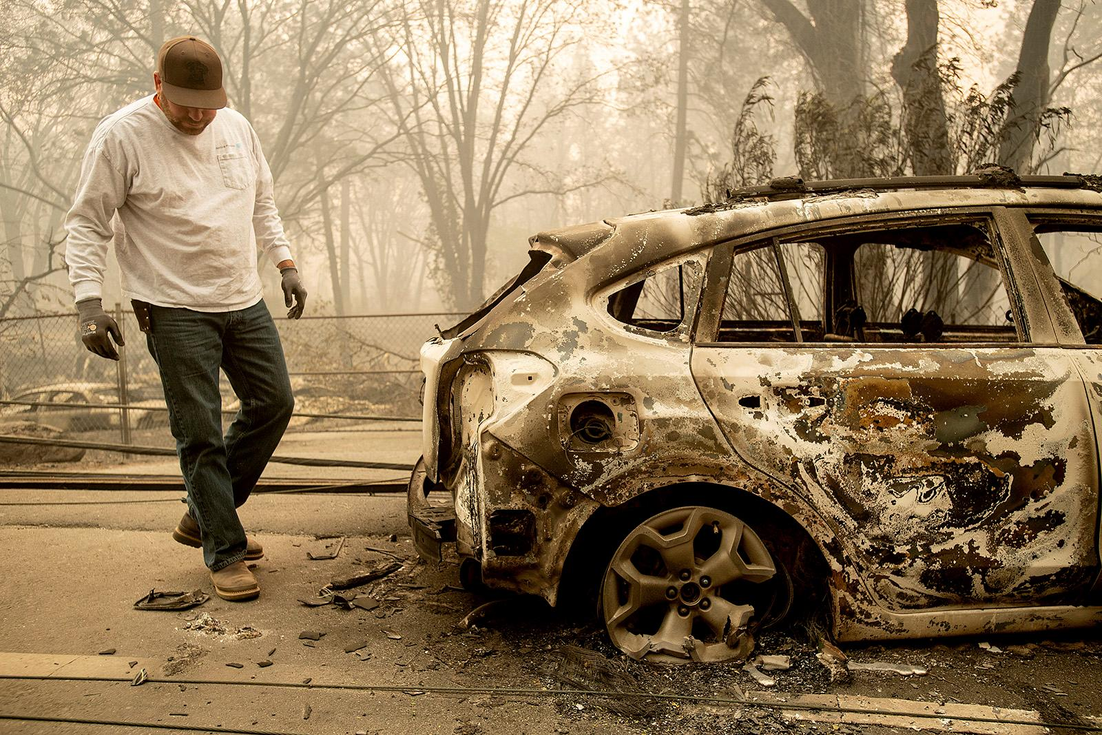 Eric England searches through a friend's vehicle on Pearson Rd. after the wildfire burned through Paradise, Calif., on Saturday, Nov. 10, 2018.  Not much is left in Paradise after a ferocious wildfire roared through the Northern California town as residents fled and entire neighborhoods are leveled. (AP Photo/Noah Berger)