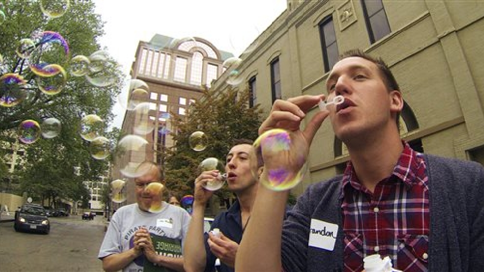 Brandon Herr, right, and Matt Antonczyk blow bubbles at a rally Monday, Aug. 25, 2014 in Milwaukee as gay couples and their supporters board a bus for a trip to Chicago for a key hearing in the fight against same-sex marriage bans. On Tuesday the 7th Circuit Court of Appeals in Chicago will hear oral arguments in a combined appeal from Wisconsin and Indiana where same-sex marriage were ruled unconstitutional in June. (AP Photo/Carrie Antlfinger)
