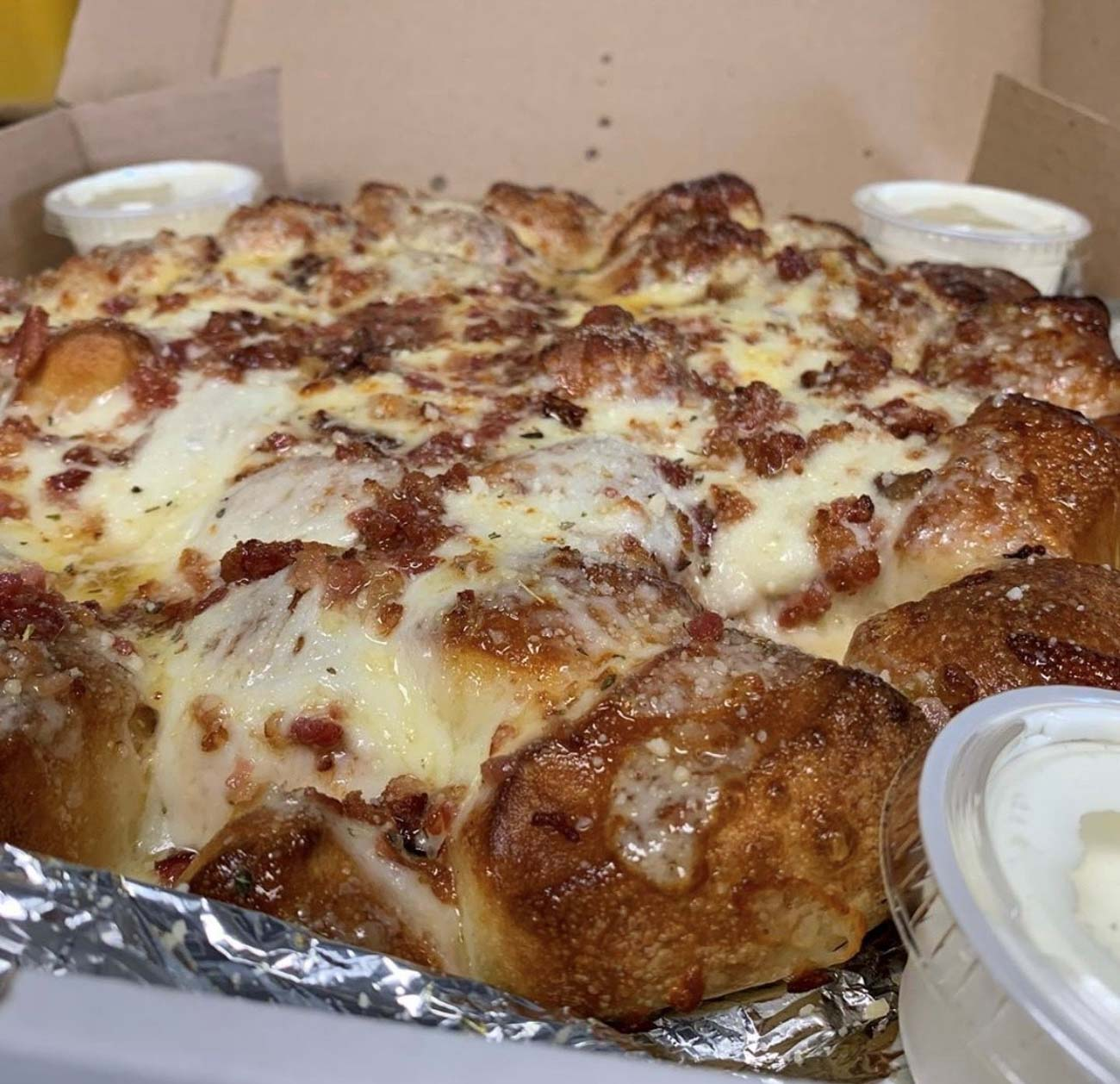 Drip Too Hard: their Cheesy Garlic Drips topped with bacon and a side of homemade ranch dipping sauce / Image courtesy of Poseidon's Pizza Company // Published: 7.8.20