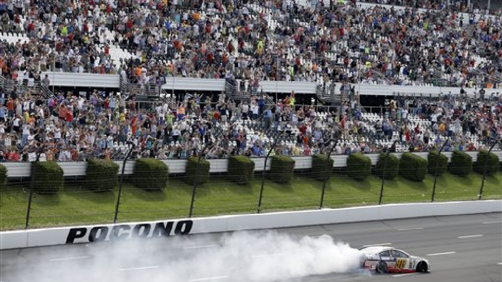 Driver Dale Earnhardt Jr. (88) does a burnout in front fans after winning the NASCAR Sprint Cup series Pocono 400 auto race, Sunday, June 8, 2014, in Long Pond, Pa. (AP Photo/Mel Evans)