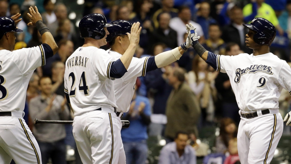 Milwaukee Brewers' Jean Segura (9) is congratulated by teammates Lyle Overbay (24), Khris Davis (18) and Kyle Lohse after hitting a three-run home run during the second inning of a baseball game against the San Diego Padres, Wednesday, April 23, 2014, in Milwaukee. (AP Photo/Morry Gash)