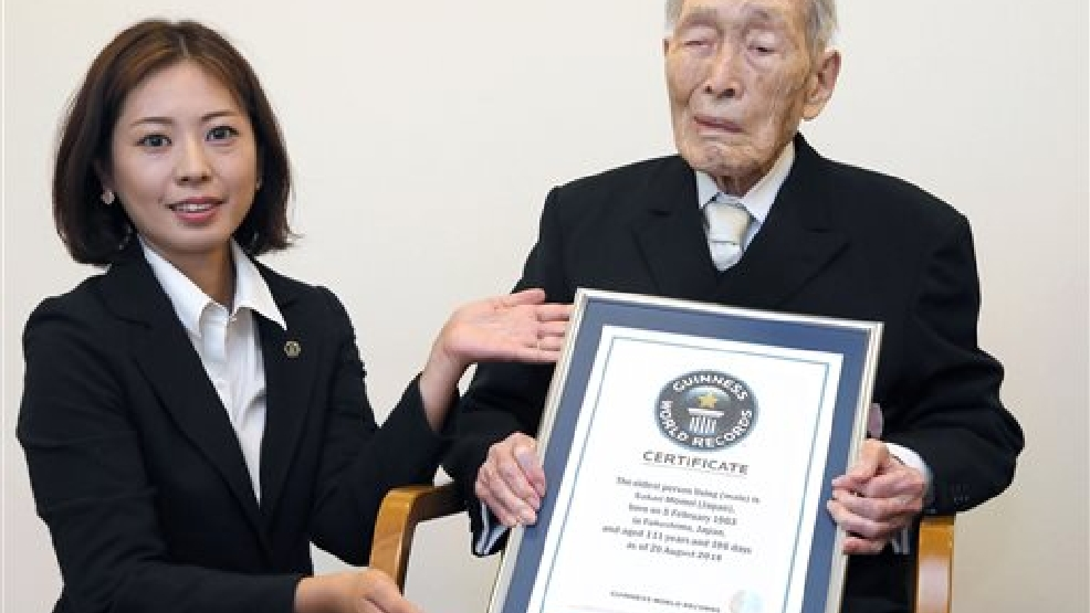 Sakari Momoi, a 111-year-old Japanese retired educator, poses for a photo after receiving a certificate from a Guinness World Records official, left, in Tokyo Wednesday, Aug. 20, 2014. Momoi was recognized as the world's oldest living man on Wednesday, succeeding Alexander Imich of New York, who died in April at the age of 111 years, 164 days. (AP Photo/Kyodo News)