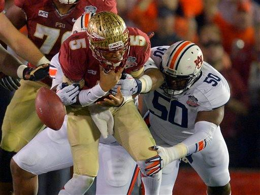Florida State's Jameis Winston fumbles the ball as he is hit by Auburn's Ben Bradley (50)and Angelo Blackson during the first half of the NCAA BCS National Championship college football game Monday, Jan. 6, 2014, in Pasadena, Calif.