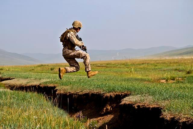 U.S. Marine Lance Cpl. Nicholas Moore jumps over a ditch during a cordon and search event during Khaan Quest 2013 at Five Hills Training Area in Mongolia, Aug. 08, 2013.