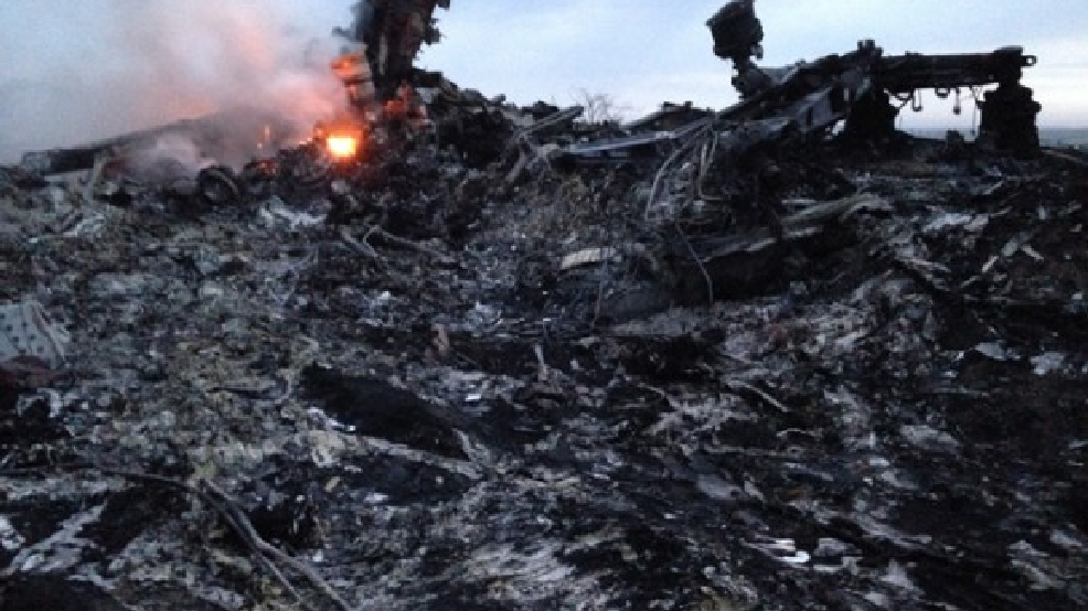 Smoke rises up at a crash site of a passenger plane, near the village of Grabovo, Ukraine, Thursday, July 17, 2014. A Ukrainian official said a passenger plane carrying 295 people was shot down Thursday as it flew over the country and plumes of black smoke rose up near a rebel-held village in eastern Ukraine. Malaysia Airlines tweeted that it lost contact with one of its flights as it was traveling from Amsterdam to Kuala Lumpur over Ukrainian airspace. (AP Photo/Dmitry Lovetsky)