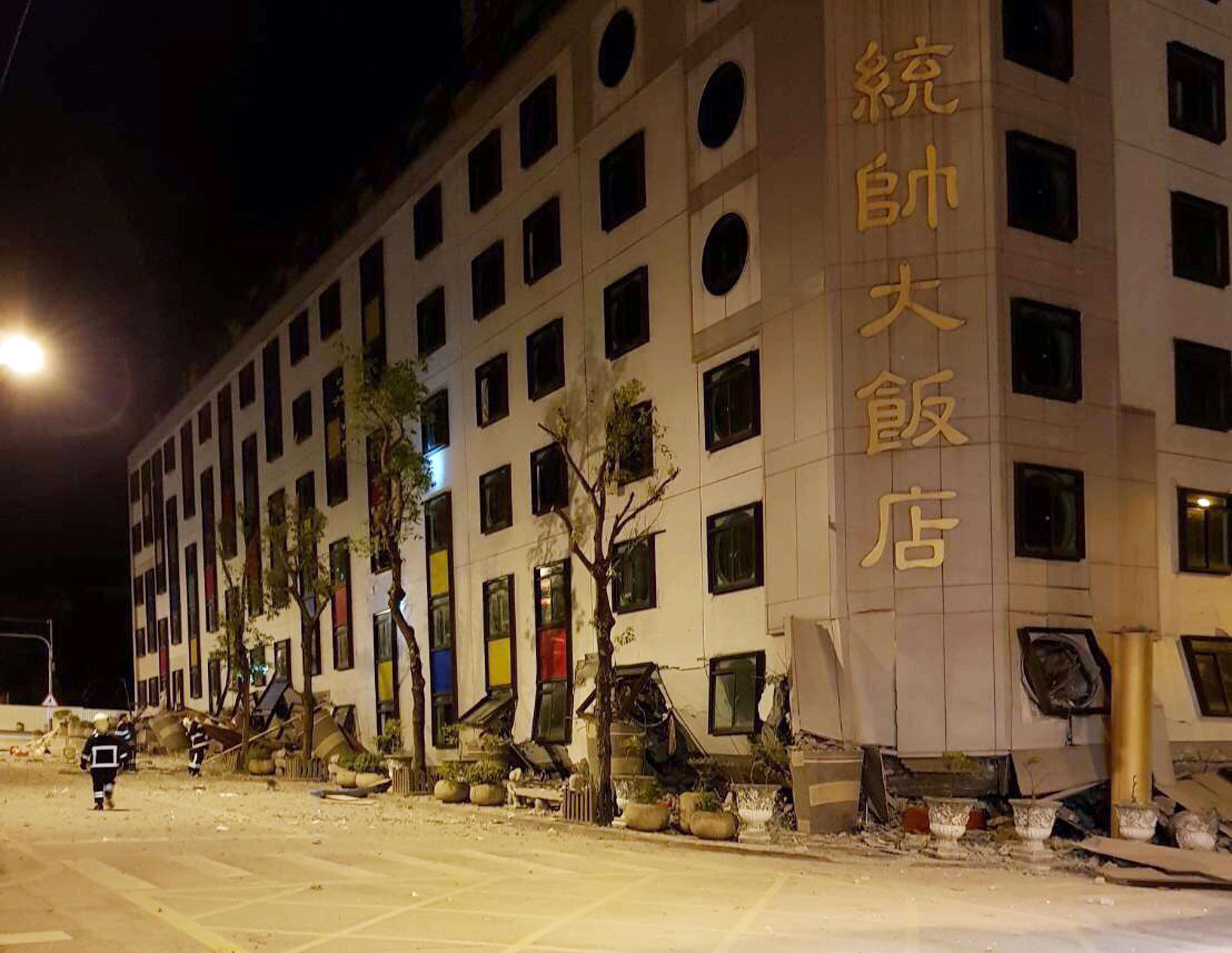In this photo released by Hualien County Fire Bureau, debris around a building as rescue workers gain entry after the building collapsed onto its side following an early morning earthquake in Hualien County, eastern Taiwan, Wednesday, Feb. 7 2018. A 6.4-magnitude earthquake has struck eastern Taiwan. (Hualien County Fire Bureau via AP)