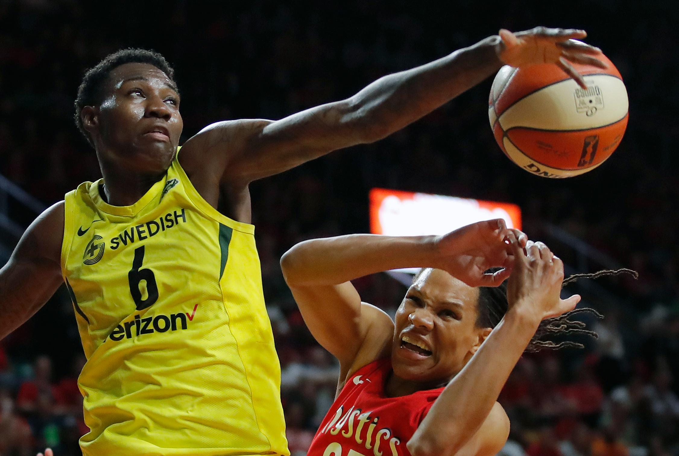 Seattle Storm forward Natasha Howard (6) and Washington Mystics forward Monique Currie (25) fight for the ball during the second half of Game 3 of the WNBA basketball finals, Wednesday, Sept. 18 2018, in Fairfax, Va. The Seattle Storm won 98-82. (AP Photo/Carolyn Kaster)