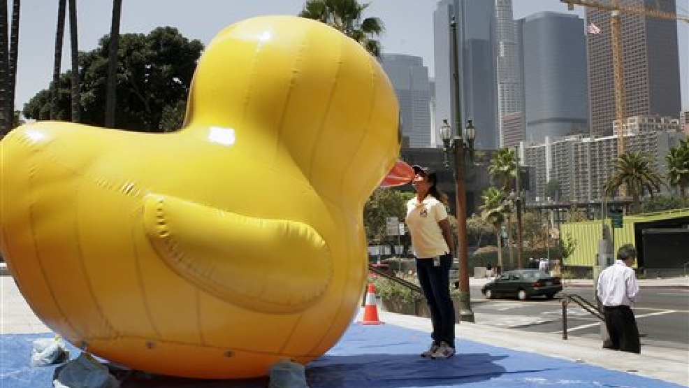Sheila Gonzales, a community program manager for the Port of Los Angeles, kisses an inflatable rubber duck on the steps of City Hall on Friday, Aug. 8, 2014. The duck is promoting the Tall Ships Festival L.A., a daylong celebration of tall ships on Aug. 20, 2014. This year's festival features an oversized duck by Dutch artist Florentijn Hofman, whose Rubber Duck project has brought the world's largest ducks to harbors across the world, including Japan, Brazil, Australia and Taiwan. (AP Photo/Matt Hamilton)