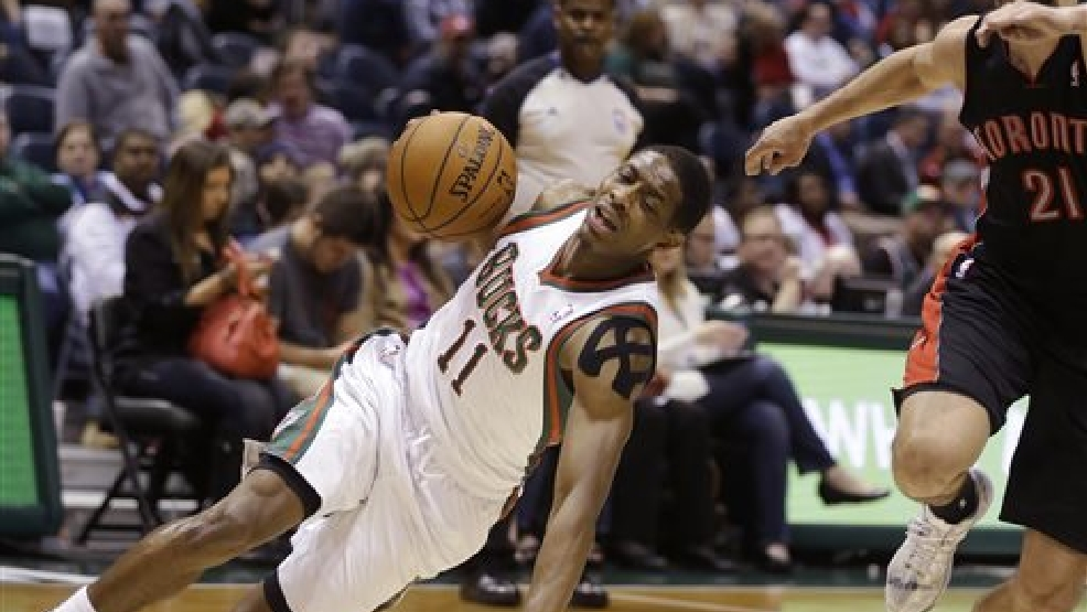 Milwaukee Bucks' Brandon Knight (11) slips while driving against Toronto Raptors' Greivis Vasquez during the second half of an NBA basketball game Saturday, April 5, 2014, in Milwaukee. (AP Photo/Jeffrey Phelps)