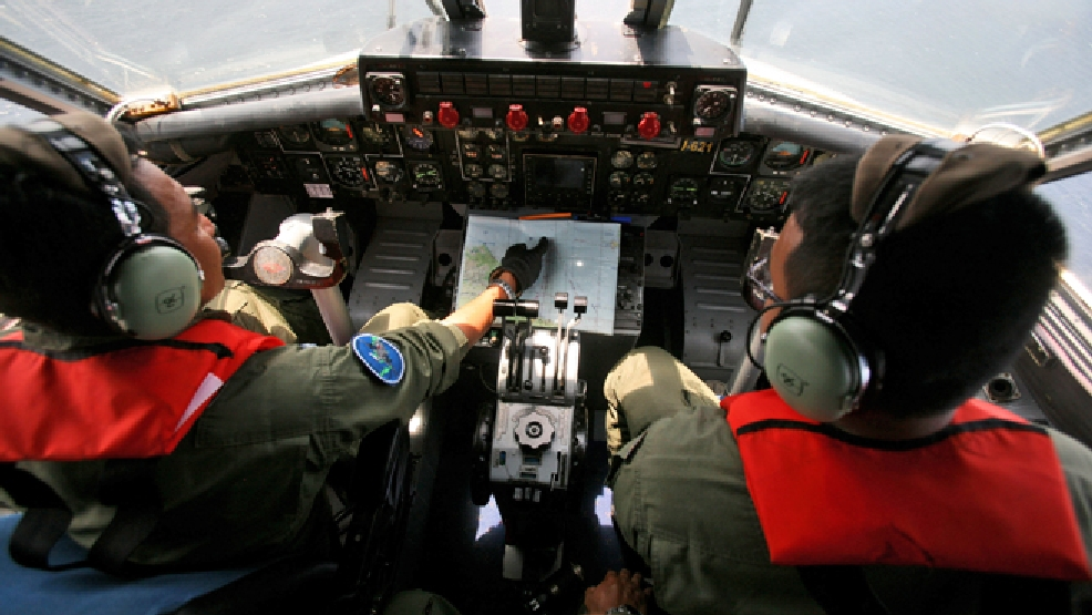 Indonesian Navy pilots Maj. Bambang Edi Saputro, left, and 2nd Lt. Tri Laksono check their map during a search operation for the missing Malaysian Airlines Boeing 777 over the waters bordering Indonesia, Malaysia and Thailand near the Malacca straits on Monday, March 10, 2014. (AP Photo/Binsar Bakkara)