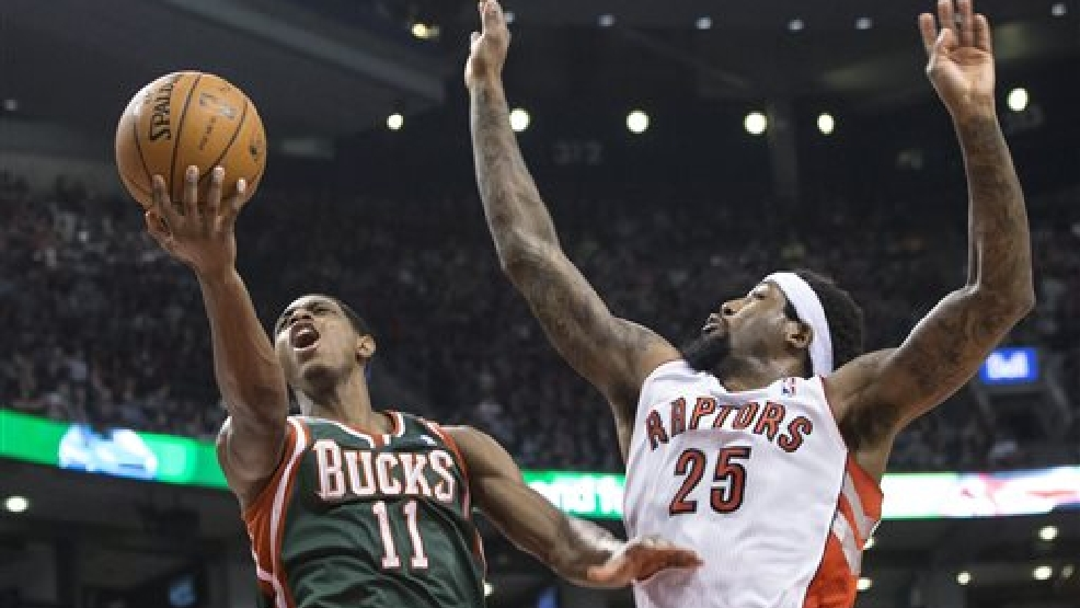 Milwaukee Bucks' Brandon Knight, left, is fouled by Toronto Raptors' John Salmons during first half NBA basketball action in Toronto on Monday, April 14, 2014. (AP Photo/The Canadian Press, Chris Young)