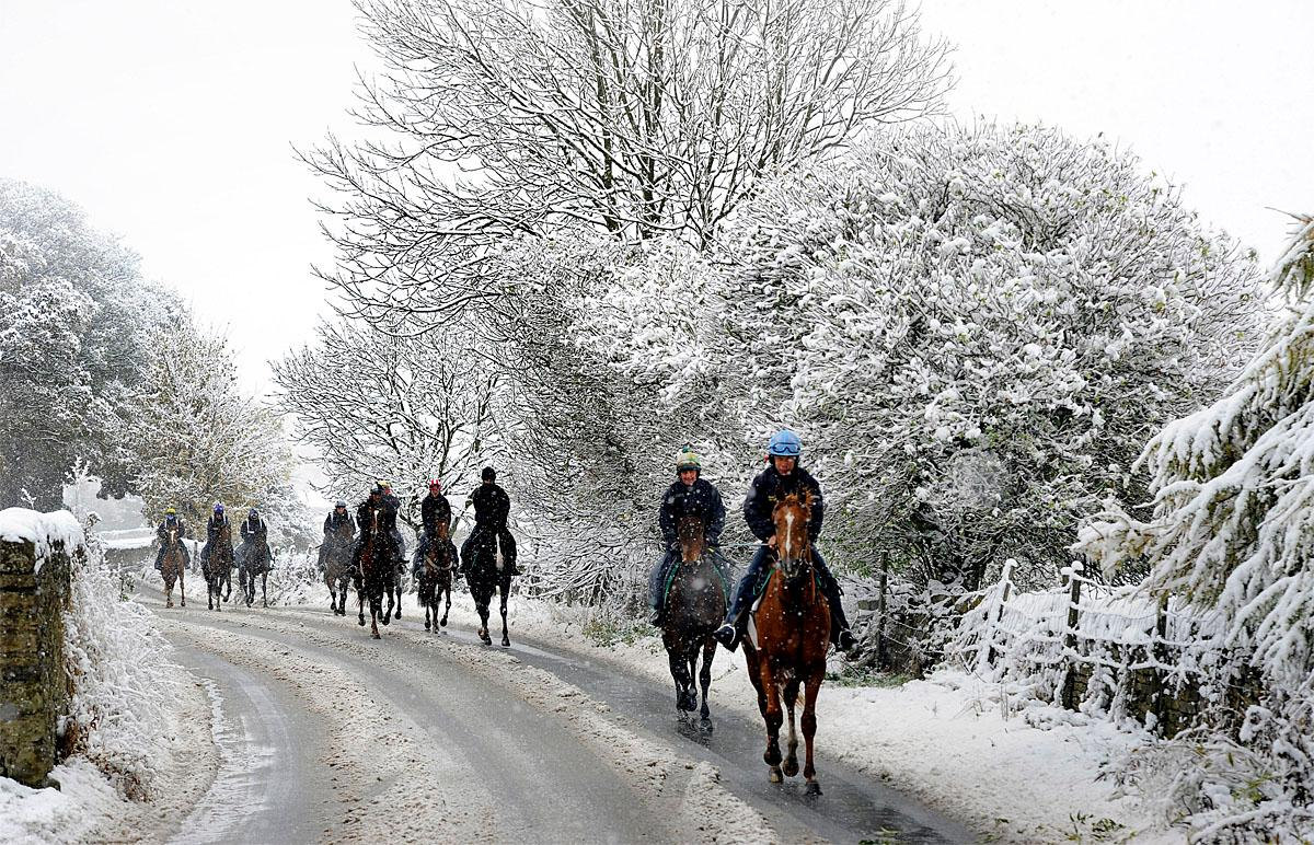People ride horses during snowfall near Middleham, north England, Wednesday Nov. 9, 2016. Snowfall overnight covered northern parts of Britain. (John Giles/PA via AP)