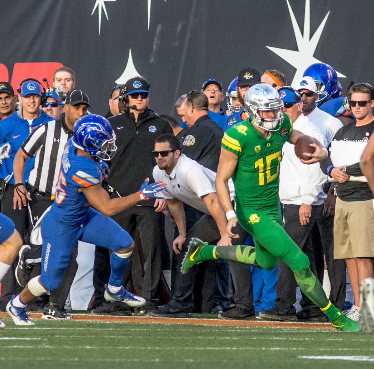 Oregon quarterback Justin Herbert (#10) sprints away from a Boise State defender.The Boise State Broncos defeated the Oregon Ducks 38 to 28 in the 2017 Las Vegas Bowl at Sam Boyd Stadium in Las Vegas, Nevada on Saturday December 17, 2017. The Las Vegas Bowl served as the first test for Oregon's new Head Coach Mario Cristobal following the loss of former Head Coach Willie Taggart to Florida State University earlier this month. Photo by Ben Lonergan, Oregon News Lab