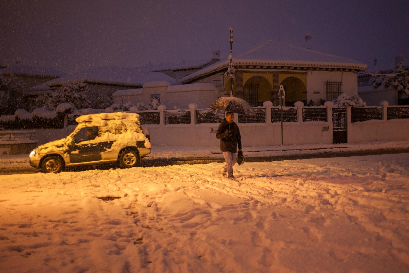 A man walks through a street covered with snow in the city of Ronda, southern Spain, Thursday, Jan. 19, 2017. (AP Photo/Javier Gonzalez)