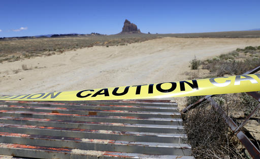 An access road to the Shiprock pinnacle is taped off along Navajo Route 13, just a few miles from where Ashlynne Mike's body was discovered, in south of Shiprock, N.M., on Tuesday, May 3, 2016. Police gleaned some information about the suspect from the younger brother of Ashlynne, whose body was found Tuesday near the distinct rock formation that the rural town of Shiprock, is named for. Authorities are poring over parts of the Navajo Nation in search of the man who snatched the children and killed Ashlynne. (Jon Austria/The Daily Times via AP) MANDATORY CREDIT
