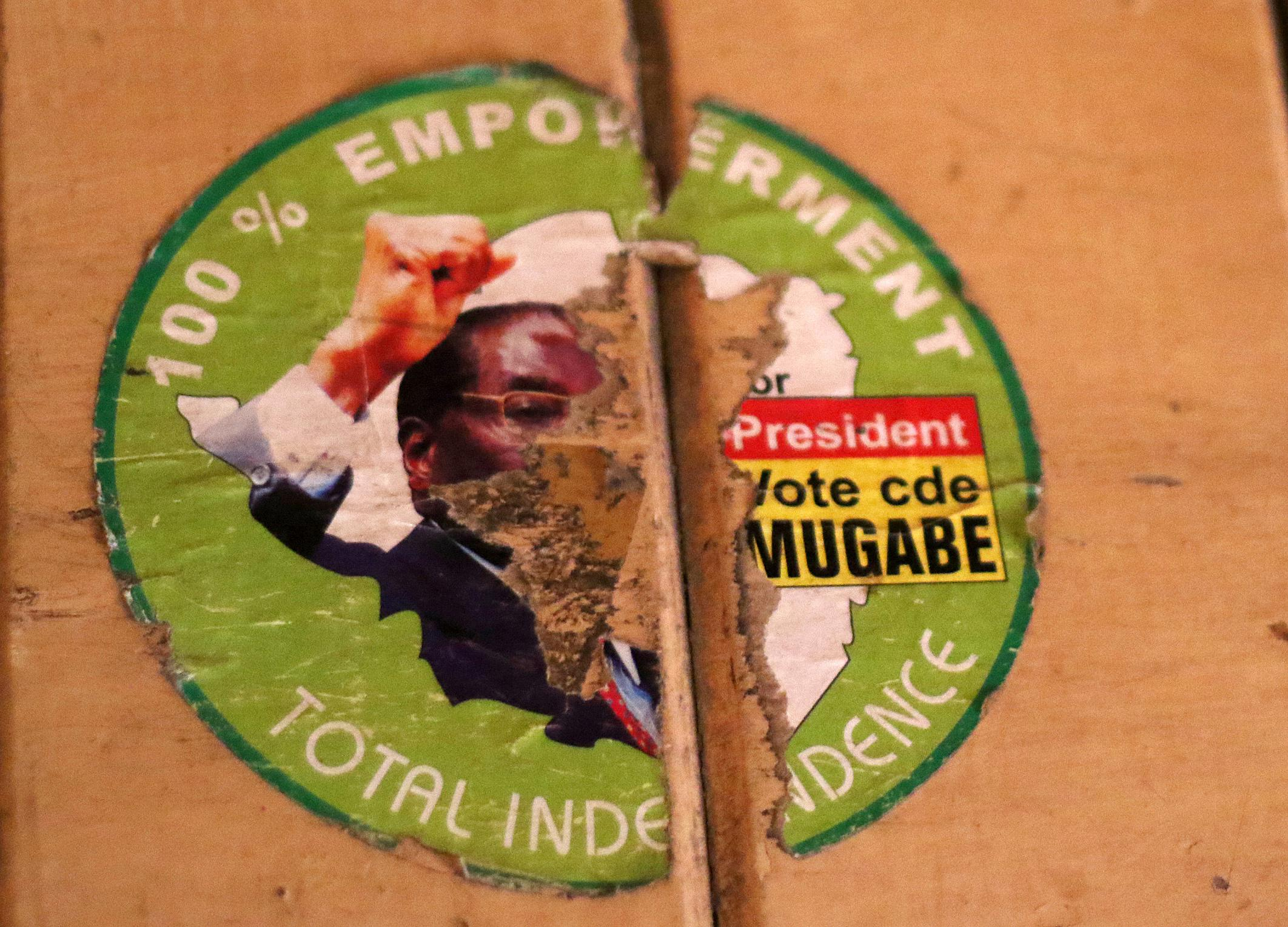 An old torn election sticker, with a portrait of Zimbabwean President Robert Mugabe, on a building in Harare Sunday, Nov. 19 2017. Zimbabwe's ruling party Central Committee begun removing Mugabe as party leader and replacing him with recently fired Vice President, Emmerson Mnangagwa. (AP Photo)