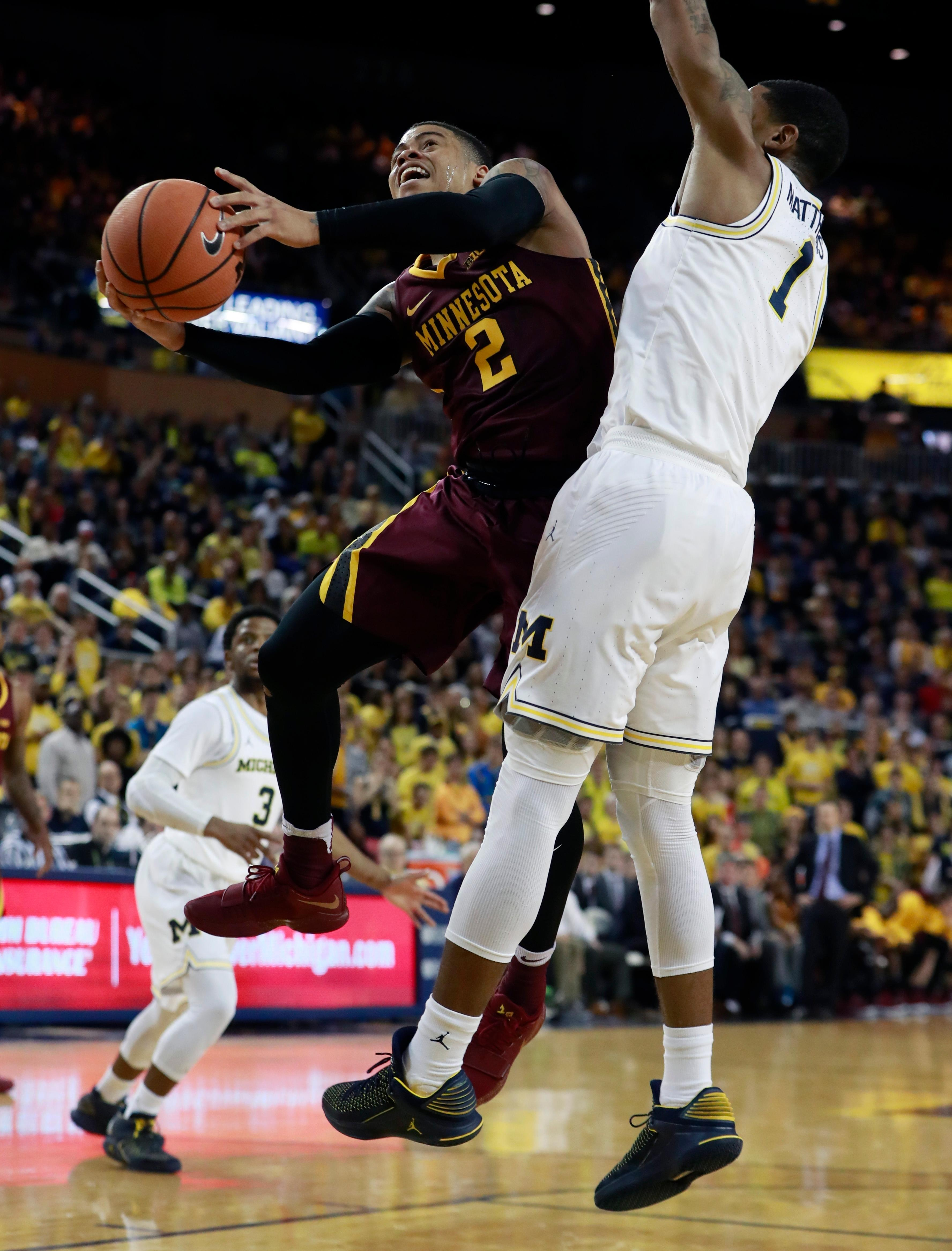 Minnesota guard Nate Mason (2) makes a layup as Michigan guard Charles Matthews (1) defends during the first half of an NCAA college basketball game, Saturday, Feb. 3,2018, in Ann Arbor, Mich. (AP Photo/Carlos Osorio)