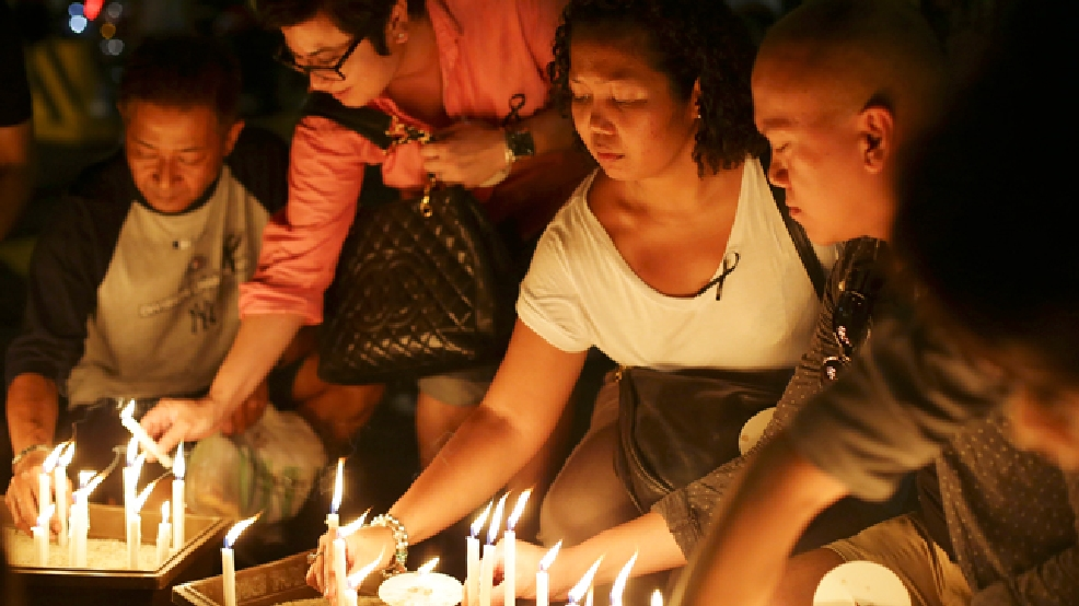 People place candles during a ceremony in memory of passengers on board the missing Malaysia Airlines Flight MH370 in Kuala Lumpur, Malaysia on Thursday, March 27, 2014. (AP Photo/Aaron Favila)