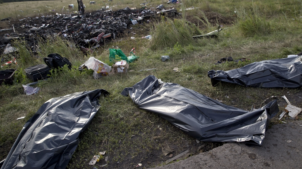 Bodies of victims are covered in plastic sacks at the crash site of Malaysia Airlines Flight 17 near the village of Hrabove, eastern Ukraine, Saturday, July 19, 2014. World leaders demanded Friday that pro-Russia rebels who control the eastern Ukraine crash site of Malaysia Airlines Flight 17 give immediate, unfettered access to independent investigators to determine who shot down the plane. (AP Photo/Vadim Ghirda)