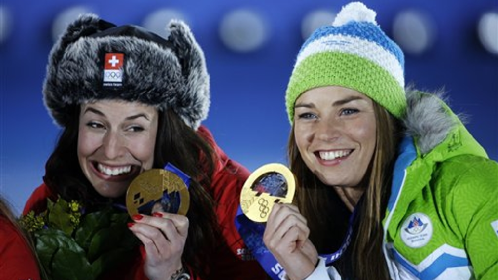 Dominique Gisin of Switzerland, left, and Tina Maze of Slovenia, right, who tied for the gold medal in the women's downhill  pose during their medals ceremony at the 2014 Winter Olympics, Wednesday, Feb. 12, 2014, in Sochi, Russia. (AP Photo/David Goldman)