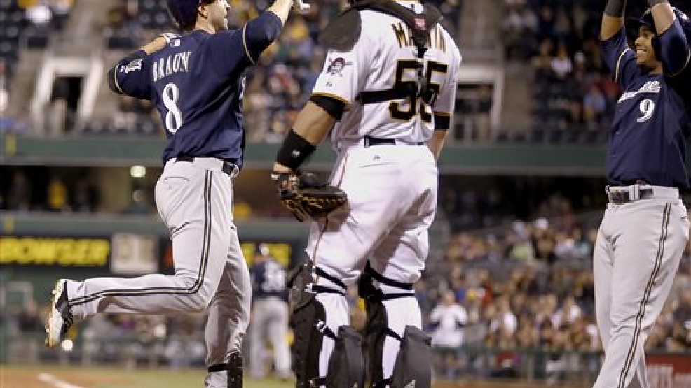 Milwaukee Brewers' Ryan Braun (8) runs to teammate Jean Segura (9) after driving him in with a two-run home run in the ninth inning of a baseball game against the Pittsburgh Pirates, Saturday, April 19, 2014, in Pittsburgh. The Brewers won 8-7. Pirates catcher Russell Martin (55) looks on. (AP Photo/Keith Srakocic)