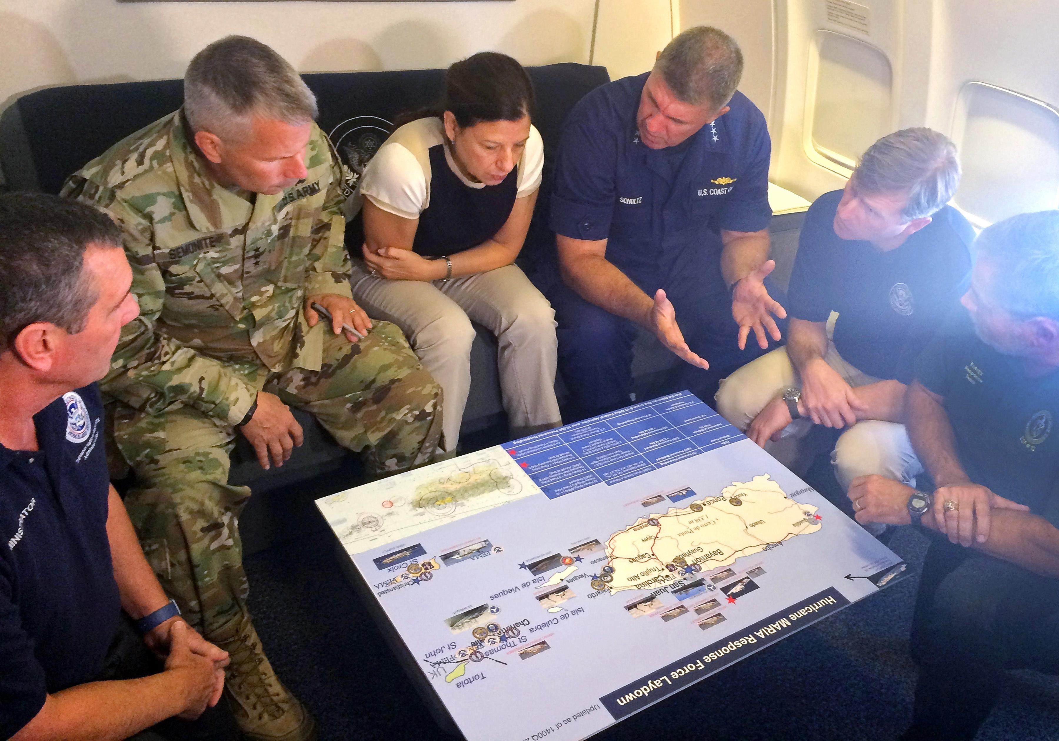 Acting Homeland Secretary Elaine Duke, center, is briefed on the Hurricane Maria response during a flight to Puerto Rico on Friday, Sept. 29, 2017.  (AP Photo/Luis Alonso Lugo)