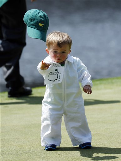 Scott Stallings's son Finn throws off his cap on the fourth green during the par three competition at the Masters golf tournament Wednesday, April 9, 2014, in Augusta, Ga.