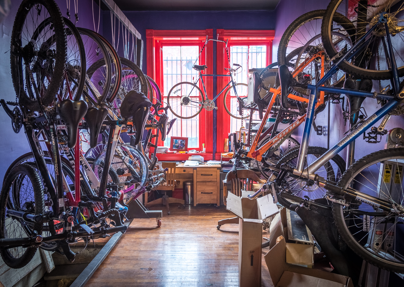 Judi LoPresti's office is situated in the back of the shop. To-be-serviced bikes hang on handmade racks, and her desk sits below her late father's bike, which is hung from the ceiling. / Image: Phil Armstrong, Cincinnati Refined // Published: 3.19.17