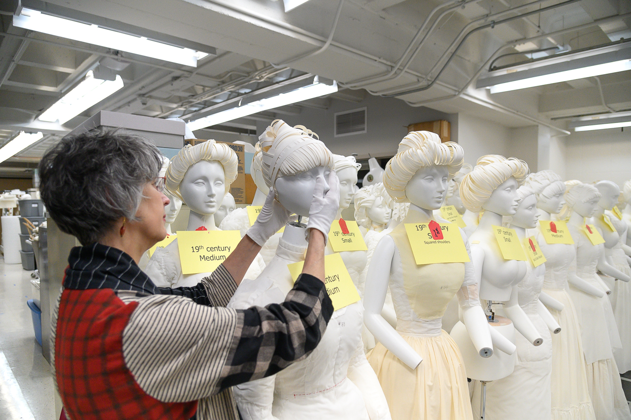The Japanese-made 19th-century mannequins are fully adjustable. Cynthia can be seen here adjusting the head of one of them. She wears protective gloves to keep them free of natural body oils. / Image: Phil Armstrong, Cincinnati Refined // Published: 2.18.20