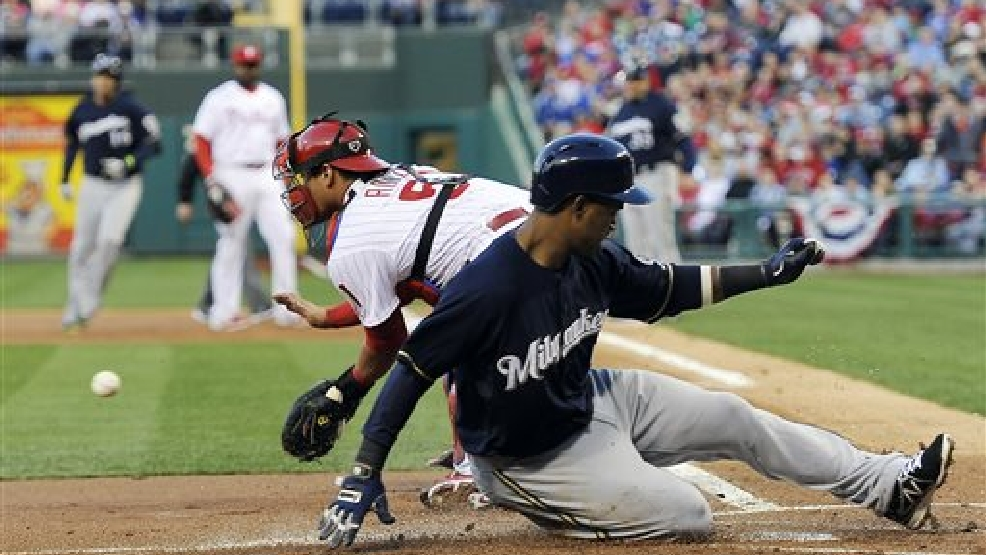 Milwaukee Brewers' Jean Segura, right, slides into home plate and score a run in front of Philadelphia Phillies' catcher Carlos Ruiz on an Aramis Ramirez RBI-single during the first inning of a baseball game on Wednesday, April 9, 2014, in Philadelphia. (AP Photo/Michael Perez)