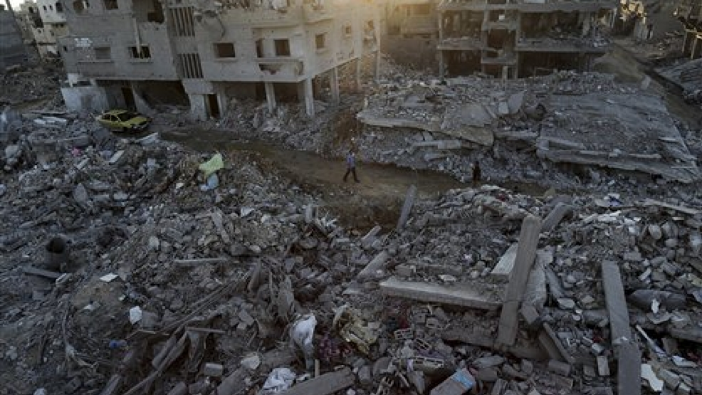 Palestinians walks next the rubble of homes destroyed by Israeli strikes in the town of Beit Hanoun, in the northern Gaza Strip, Tuesday, Aug. 12, 2014. A temporary Israel-Hamas truce was holding for a second day Tuesday as marathon, indirect negotiations on a lasting cease-fire and a long-term solution for the battered Gaza Strip were set to resume in Cairo. (AP Photo/Adel Hana)
