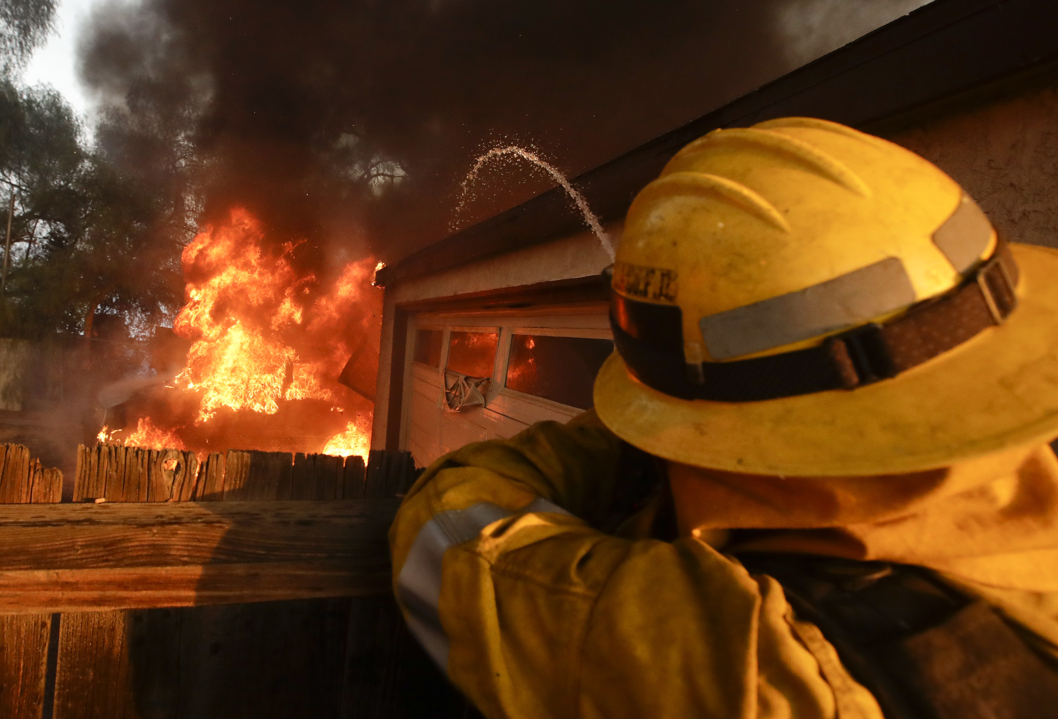 A Los Angeles County firefighter puts water a burning house in a wildfire in the Lake View Terrace area of Los Angeles Tuesday, Dec. 5, 2017. Ferocious winds in Southern California have whipped up explosive wildfires, burning a psychiatric hospital and scores of other structures. Tens of thousands of people have been ordered evacuated. (AP Photo/Chris Carlson)