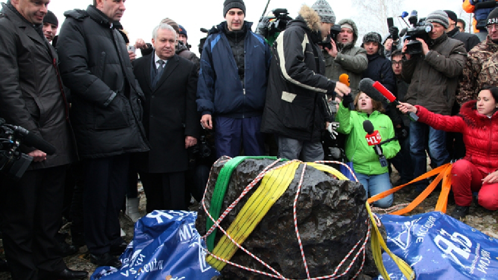 People look at what scientists believe to be a chunk of the Chelyabinsk meteor, recovered from Chebarkul Lake near Chelyabinsk, about 1500 kilometers (930 miles) east of Moscow, Russia, Wednesday, Oct. 16, 2013. (AP Photo/Alexander Firsov)