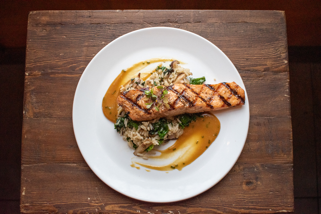 Salmon smothered in a grilled herb butter with wild rice and mushrooms and braised kale. / Image: Matt Groves // Published: 2.23.20