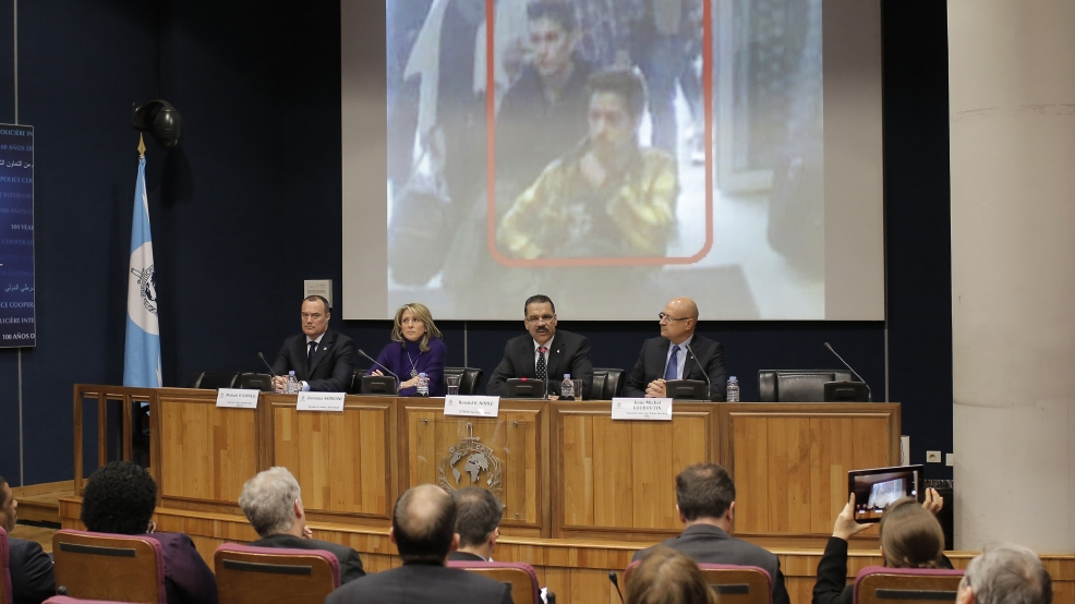 The image of two Iranian who were traveling with stolen passports on a missing Malaysia Arlines jetliner is displayed on a screen during a presser at the Interpol headquarters in Lyon, central France, Tuesday, March 11, 2014. (AP Photo/Laurent Cipriani)