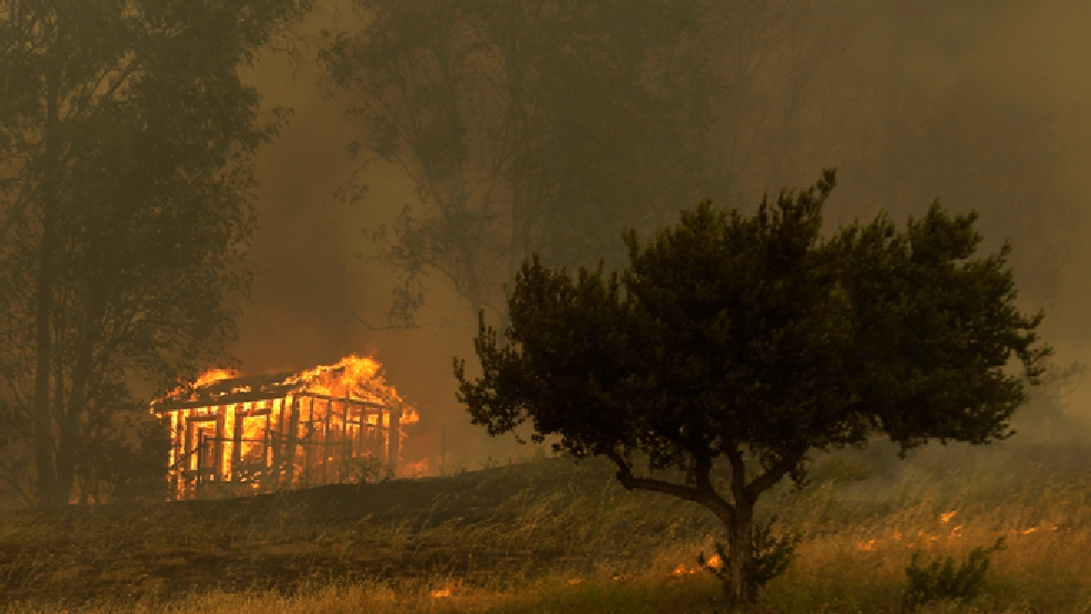 Fire engulfs a structure during a wildfire Thursday, May 15, 2014, in Escondido, Calif. (AP Photo/Gregory Bull, File)