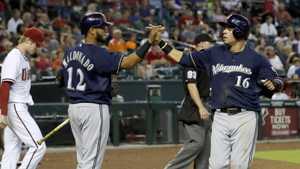 Milwaukee Brewers' Aramis Ramirez (16) celebrates his run scored with teammate Martin Maldonado (12) as Arizona Diamondbacks' Chase Anderson, left, walks nearby during the fifth inning of a baseball game on Thursday, June 19, 2014, in Phoenix. (AP Photo/Ross D. Franklin)