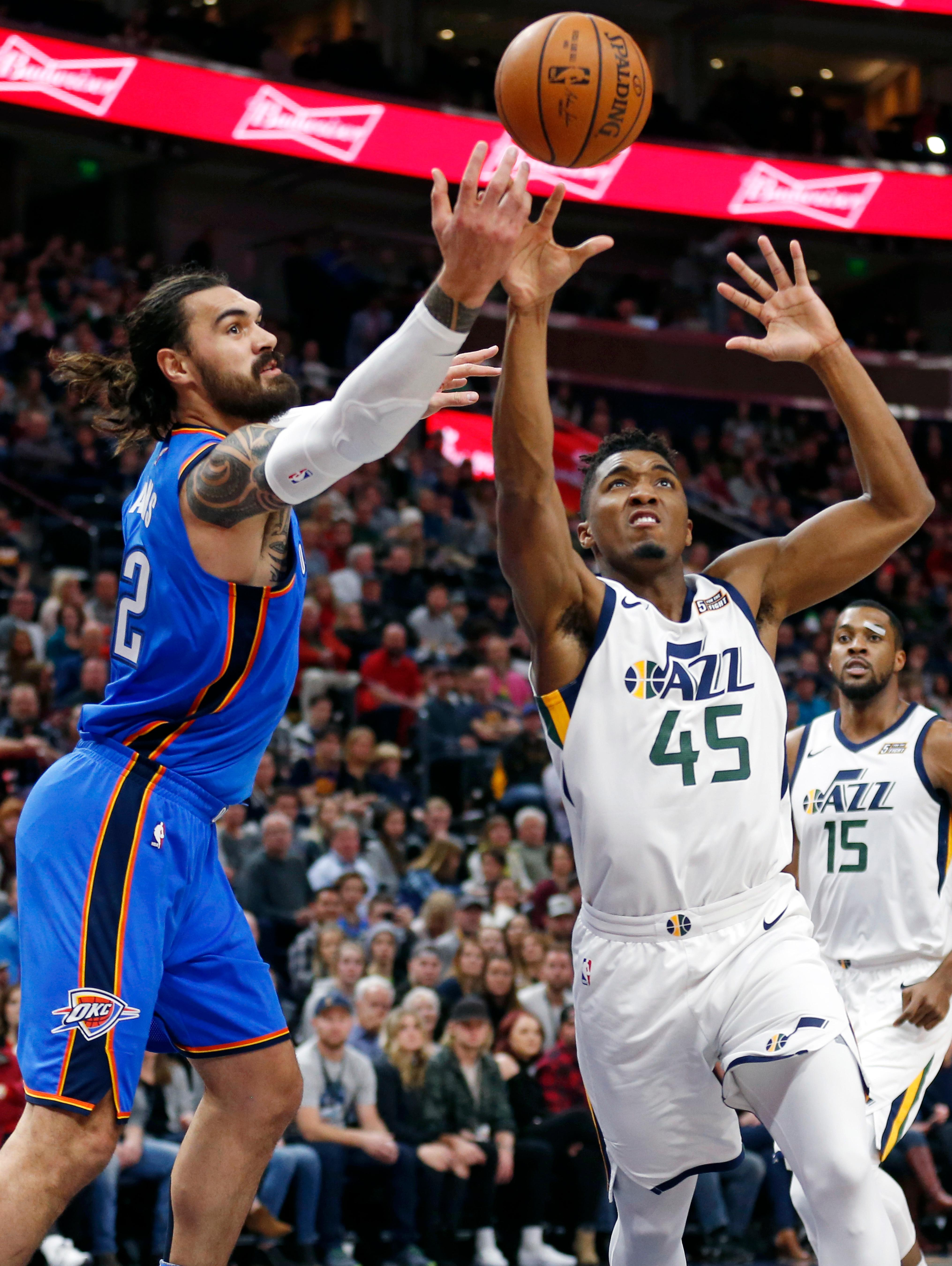 Utah Jazz guard Donovan Mitchell (45) and Oklahoma City Thunder center Steven Adams, left, battle for a rebound in the first half during an NBA basketball game Saturday, Dec. 23, 2017, in Salt Lake City. (AP Photo/Rick Bowmer)