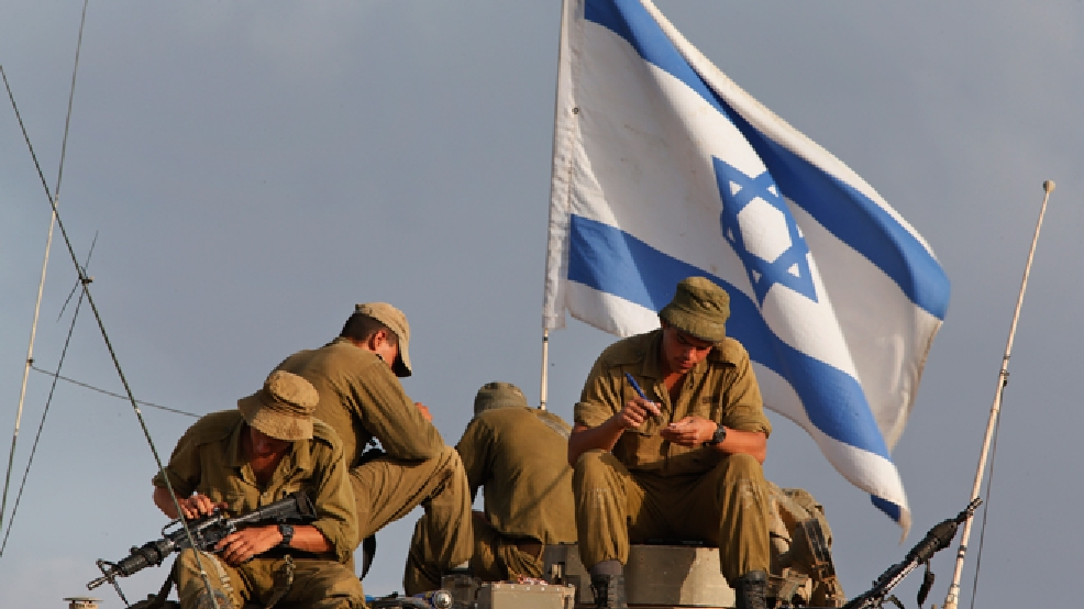 Israeli soldiers, backdropped by the national flag, sit on their armored personnel carrier as they clean their weapons, at a staging area on the Israel Gaza border on Sunday, July 13, 2014. (AP Photo/Lefteris Pitarakis)