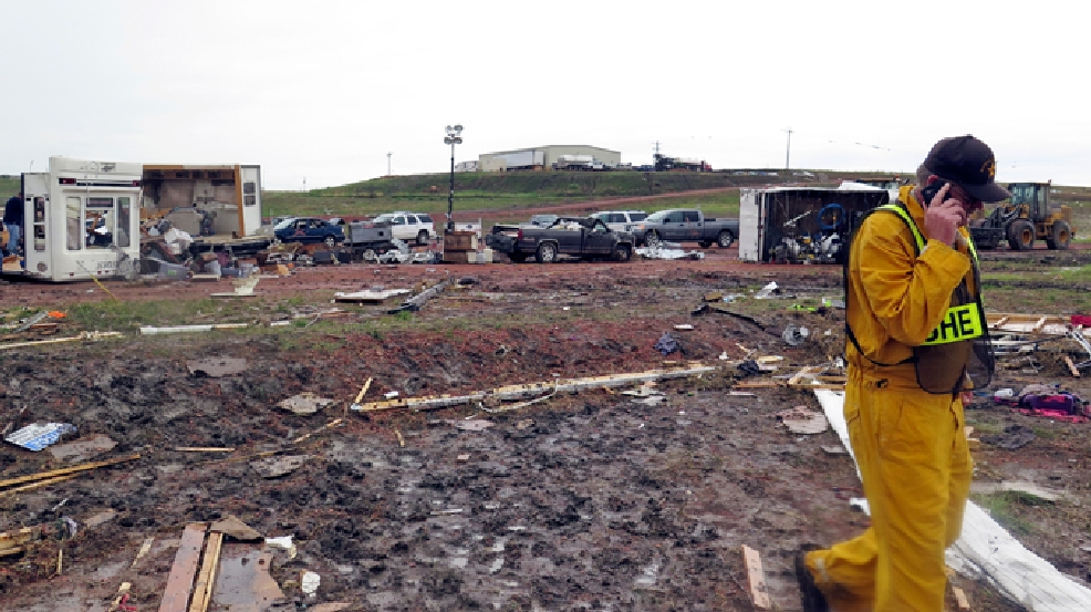 A McKenzie County Sheriff talks on a phone among scatterd debris Tuesday morning, May 27, 2014, after a tornado in Watford City, N.D. (AP Photo/Josh Wood)