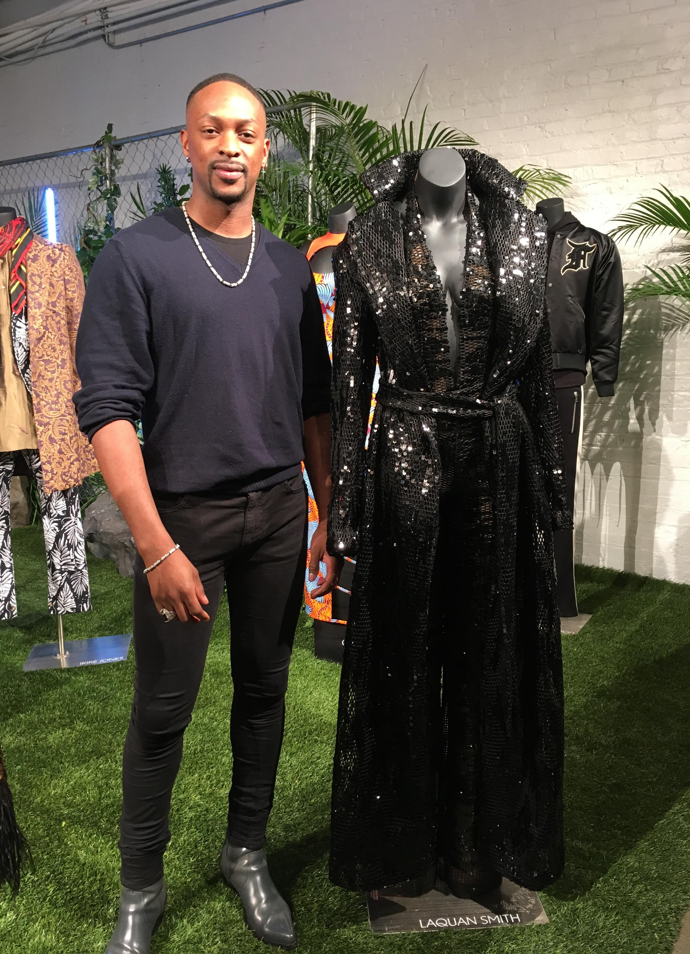 "Fashion designer LaQuan Smith stands with his jumpsuit and trench coat created for a small collection inspired by the film ""Black Panther,"" Monday, Feb. 12, 2018 in New York. The design and several others will be auctioned to benefit the nonprofit Save the Children. (AP Photo/Leanne Italie)"