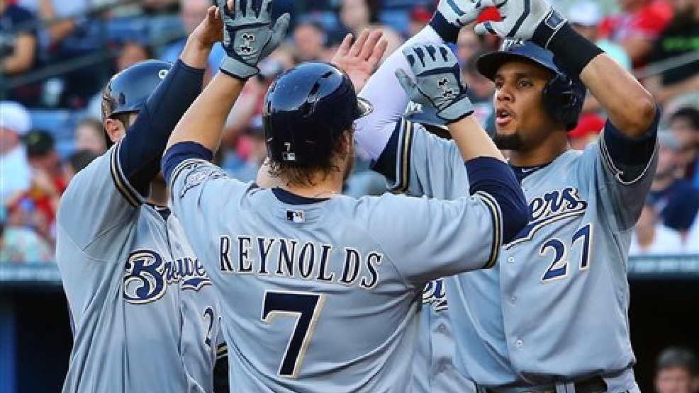 Milwaukee Brewers Mark Reynolds (7) is greeted at home by Carlos Gomez (27)  after hitting a grand slam off Atlanta Braves   pitcher Ervin Santana  during the first inning of a baseball game on Wednesday, May 21, 2014, in Atlanta.  (AP Photo/Atlanta Journal-Constitution, Curtis Compton)