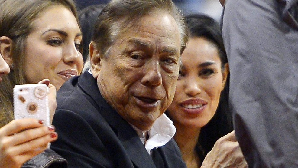 In this photo taken on Friday, Oct. 25, 2013, Los Angeles Clippers owner Donald Sterling, center, and V. Stiviano, right, watch the Clippers play the Sacramento Kings during the first half of an NBA basketball game, in Los Angeles.  (AP Photo/Mark J. Terrill)