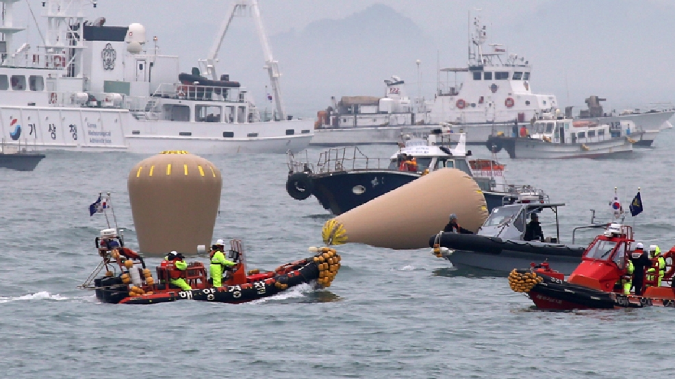 South Korean Navy officials work on buoys to mark the sunken passenger ferry, The Sewol, in the water off the southern coast near Jindo, South Korea, Friday, April 18, 2014. (AP Photo/Yonhap)