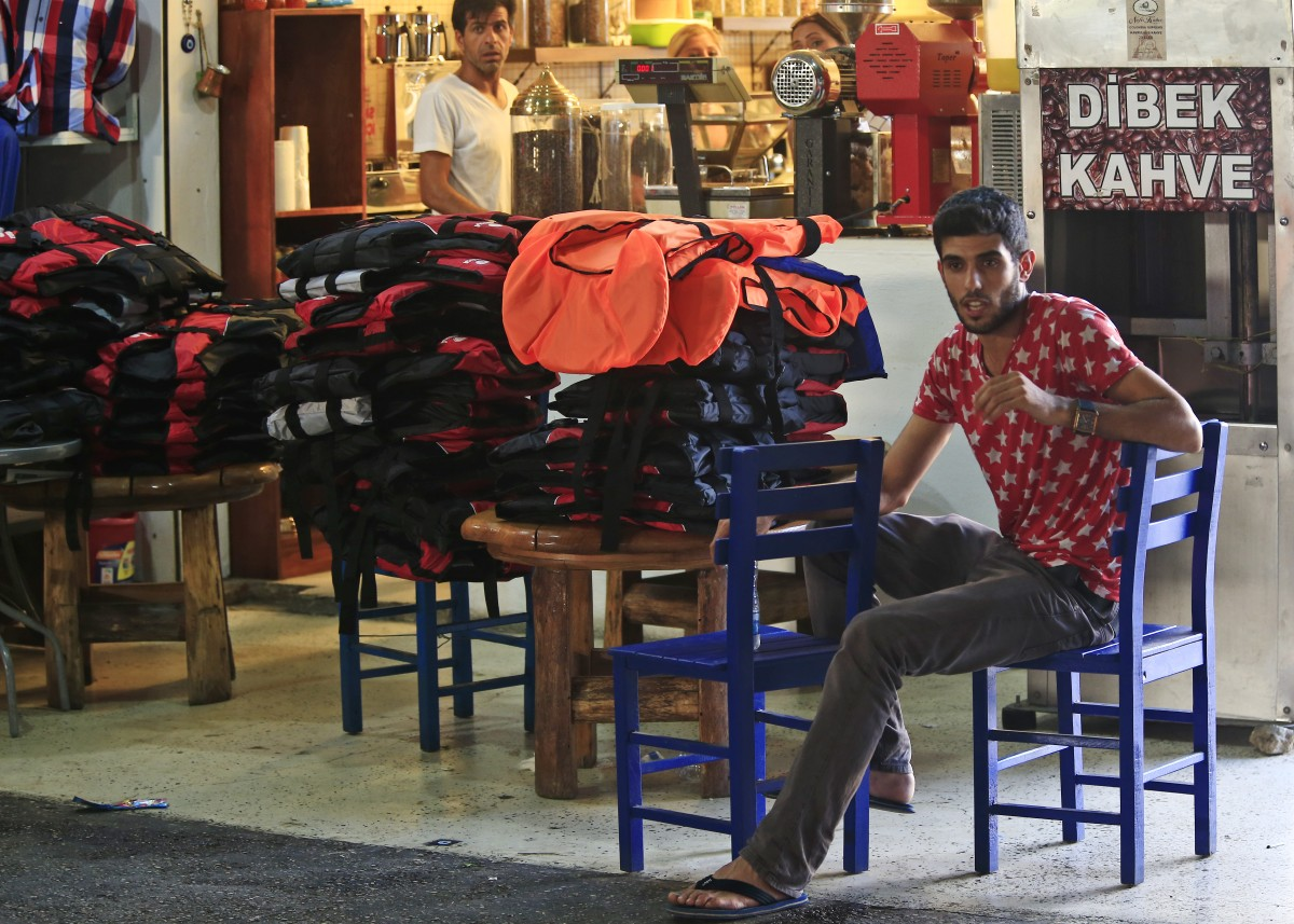 A clothing shop owner sits next to life jackets offered for sale to migrants looking to cross into boats to the Greek Island of Kos, at the bus station market of the coastal town of Bodrum, Turkey, Sunday, Aug. 16, 2015. The city of Bodrum, a magnet for wealthy tourists, is these days drawing plenty of other visitorsó migrants fleeing conflicts in the Middle East and Africa and seeking a better life in Europe. At its closest point, the Greek island of Kos is only 4 kilometers (2.5 miles) from Turkey and migrants, mostly from Syria, but also from Afghanistan, Iran and African nations often try to cross in groups upward of eight people in small inflatable plastic boats meant for a maximum of four, powered by tiny electric outboard motors and plastic paddles. (AP Photo/Lefteris Pitarakis)
