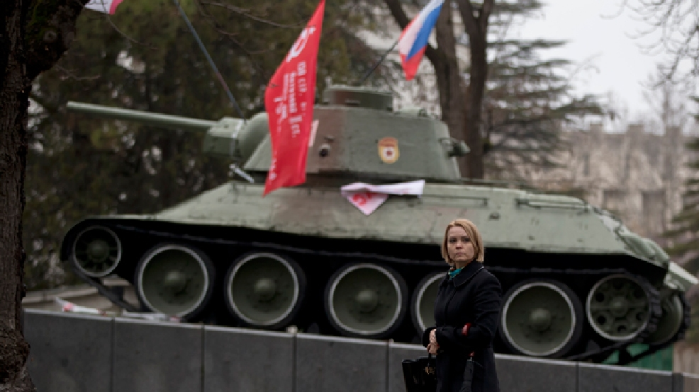 A woman passes by a WWII memorial, the actual Russian tank that was first to enter Simferopol in 1944 as the Red Army was advancing, in Simferopol, Ukraine, Friday, March 7, 2014. (AP Photo/Vadim Ghirda)