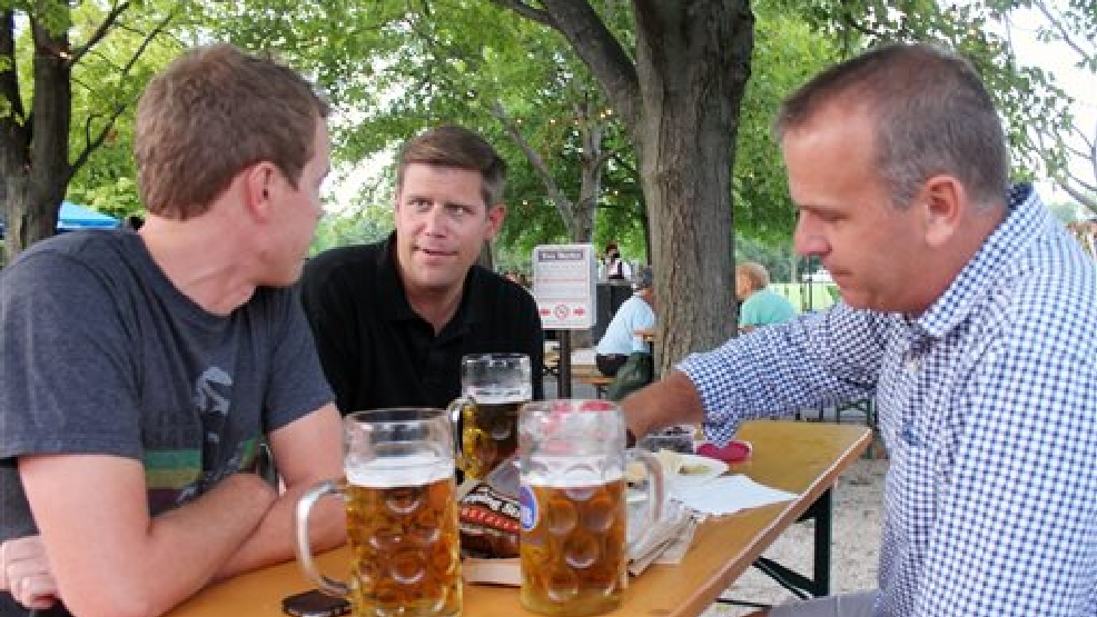 In this photo taken on Aug. 20, 2014, Scott Johnson, left, Andrew Geisler and Matthew Dusenberry enjoy oversized glass mugs of beer at Estabrook Park Beer Garden in Milwaukee. The Milwaukee County parks department has started three static outdoor beer gardens and one traveling one, as some parks departments nationwide are starting to embrace once-banned alcohol to shore up their budgets. (AP Photo/Carrie Antlfinger)