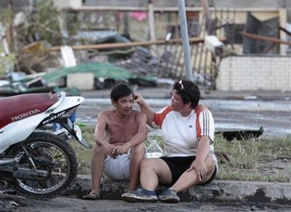 Residents sit outside their damaged house after powerful Typhoon Haiyan slammed into Tacloban city, Leyte province, central Philippines on Saturday, Nov. 9, 2013.