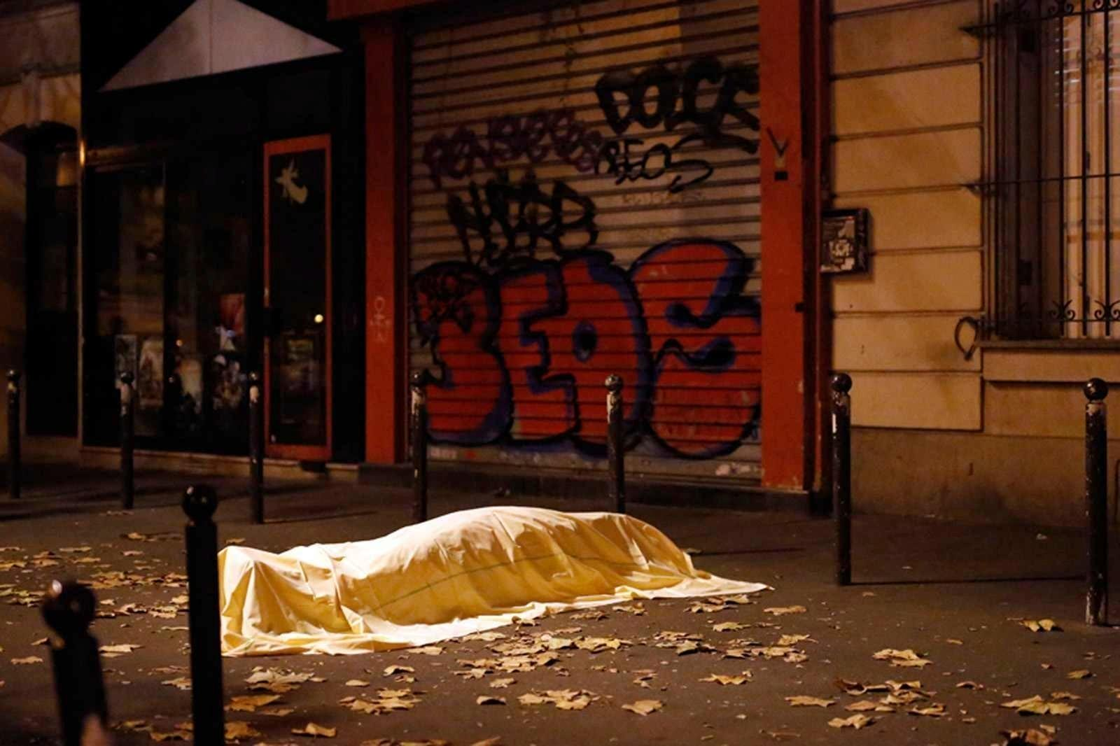 FILE - In this Friday Nov. 13, 2015 file photo a victim under a blanket lays dead outside the Bataclan theater in Paris. Salah Abdeslam, the only surviving member of the 10-man Islamic State cell that attacked Paris in November 2015, is going on trial on Monday, Feb. 5, 2018 in Belgium. The trial covers a shootout that led to his capture in March 2016.  (AP Photo/Jerome Delay, File)