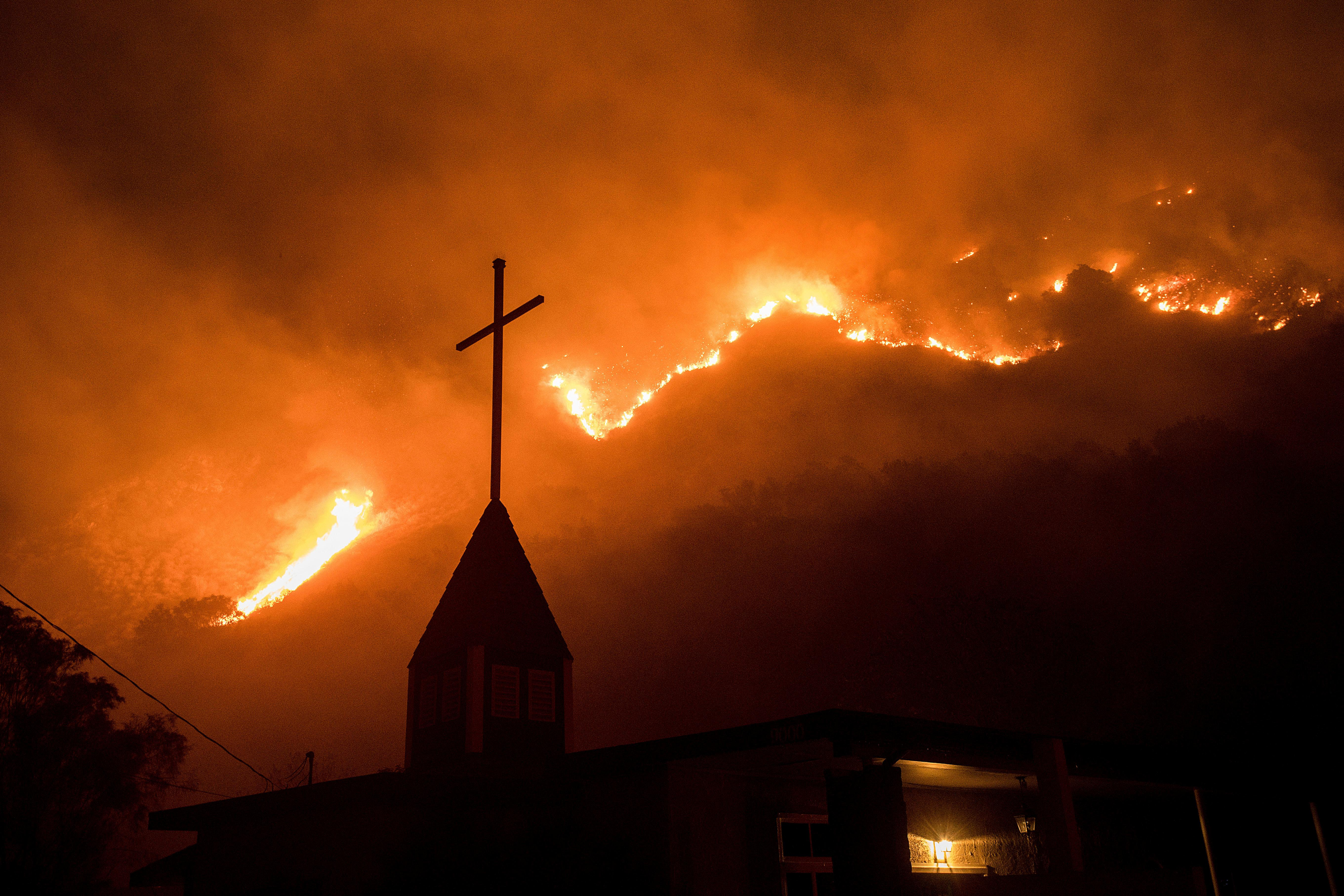 Flames from a wildfire advance down a hillside near the Springs of Life Church in Casitas Springs, Calif., on Tuesday, Dec. 5, 2017.  Wind-driven fires tore through California communities Tuesday for the second time in two months, leaving hundreds of homes feared lost and uprooting tens of thousands of people. (AP Photo/Noah Berger)